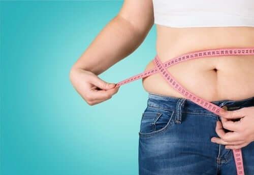 Женщина измеряет живот