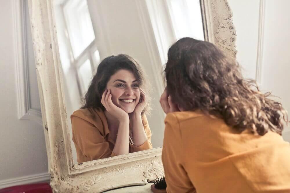 Женщина улыбается глядя в зеркало