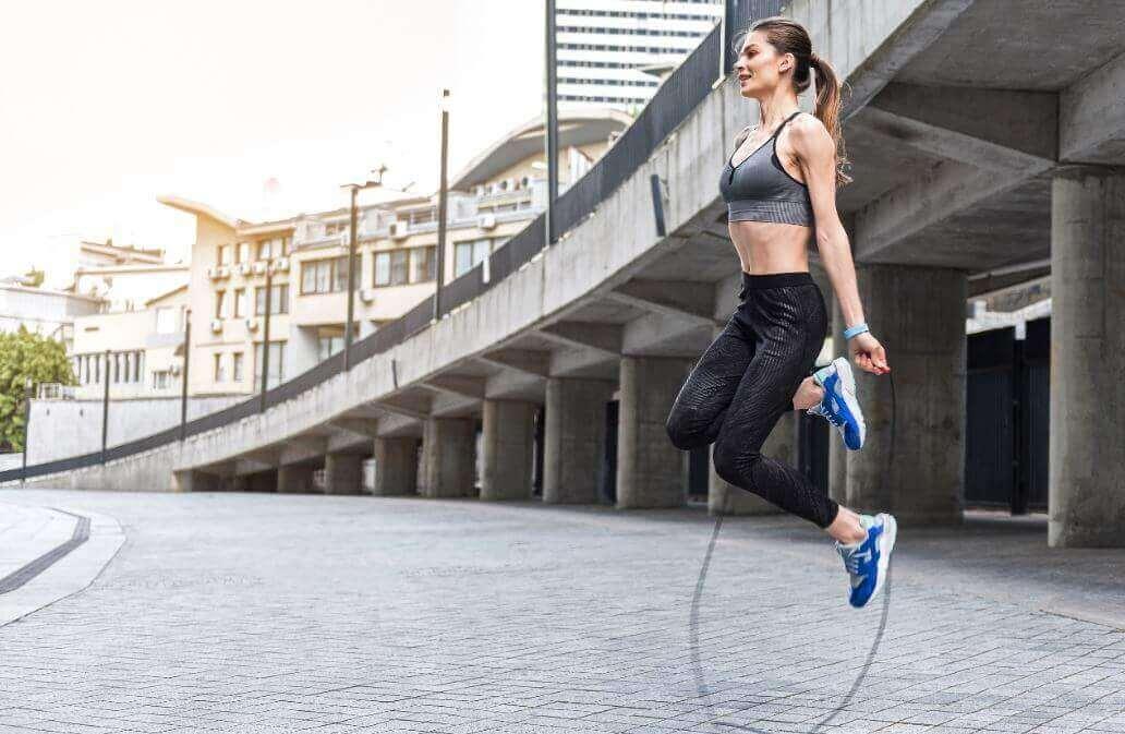 Женщина прыгает через скакалку