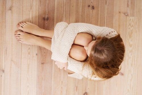 Испуганная женщина, сидящая на полу