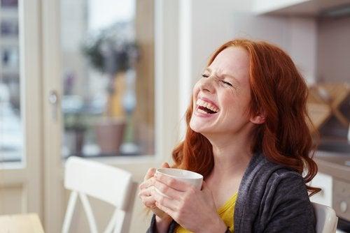 Женщина пьет кофе и смеется
