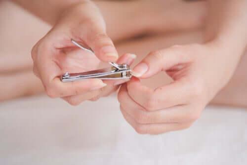 Женщина стрижет ногти