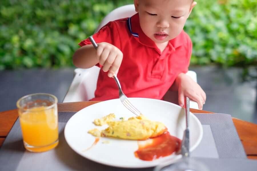 Мальчик ест омлет